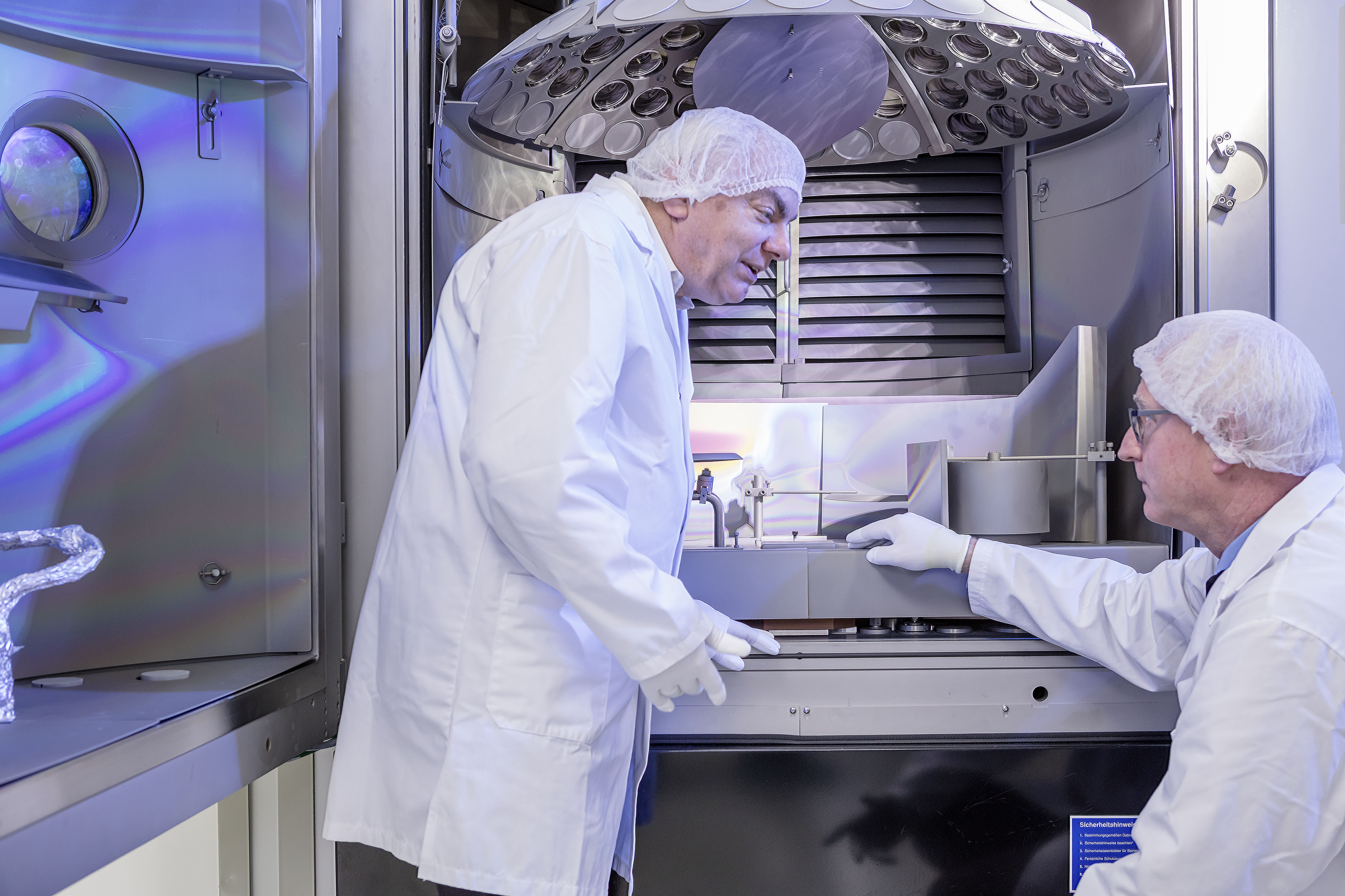 Bühler coating specialist Karl Matl and ZEISS researcher Markus Haidl work together to perfect the coating process.