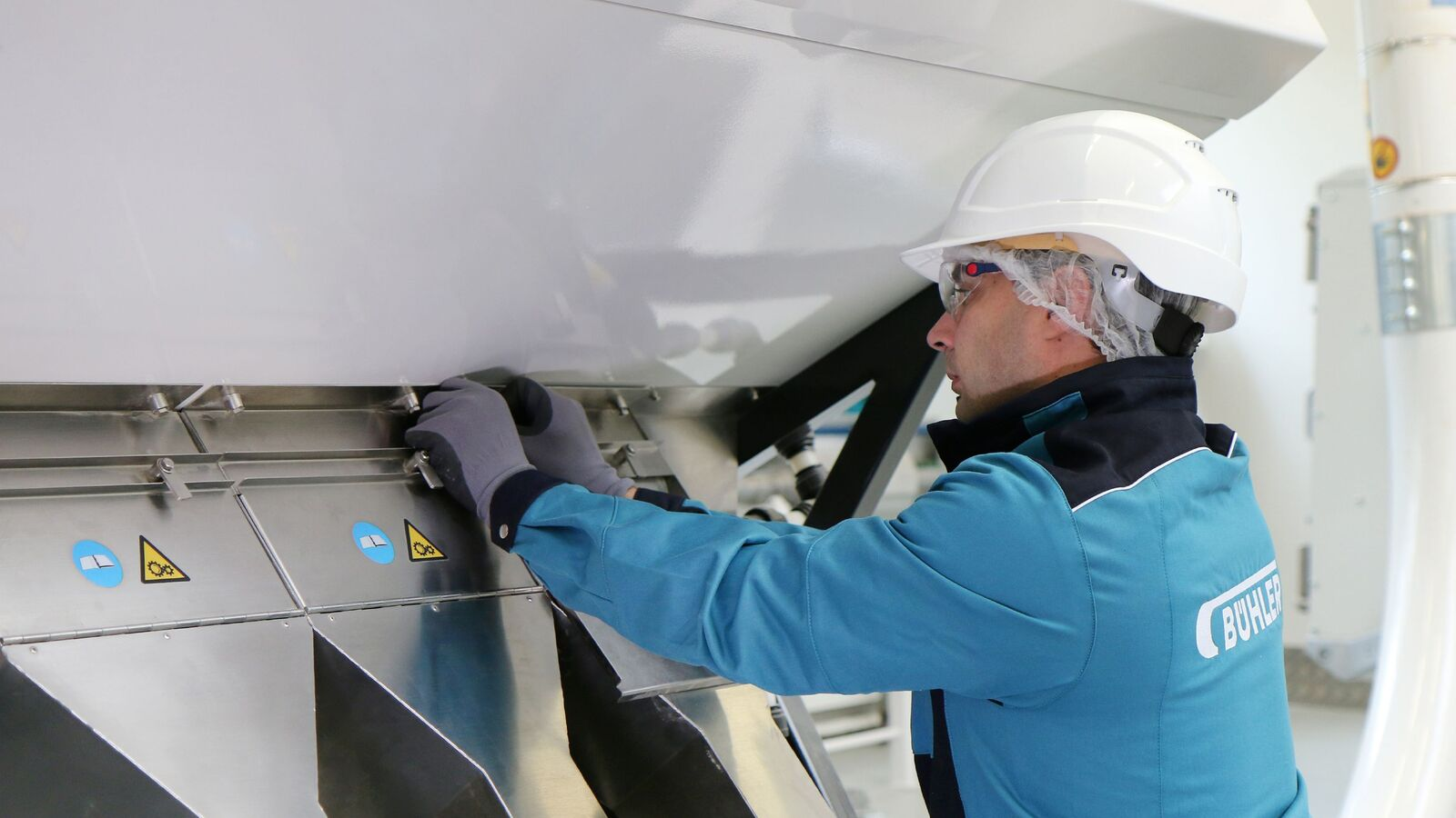 Bühler employee opening the chutes of an optical sorter SORTEX
