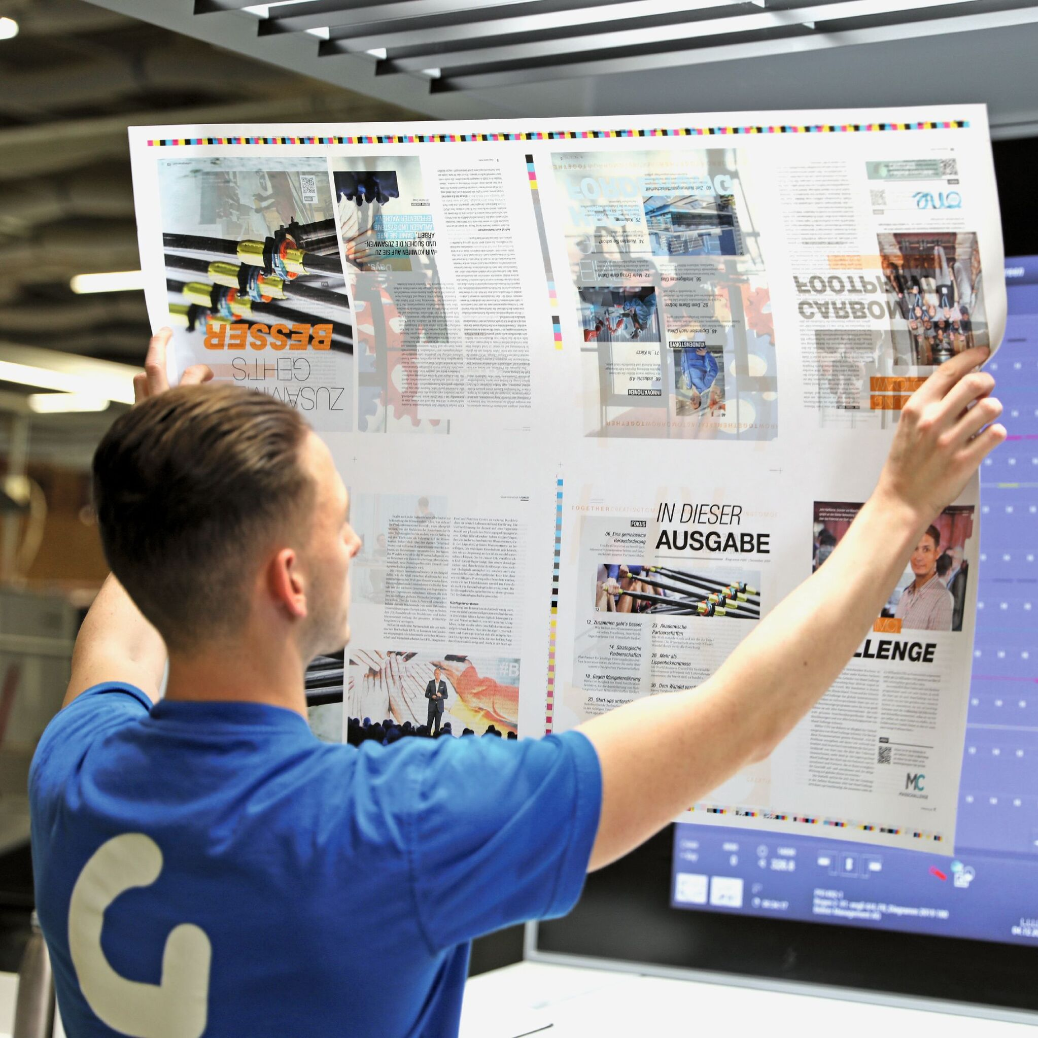 man looking at print out of magazine