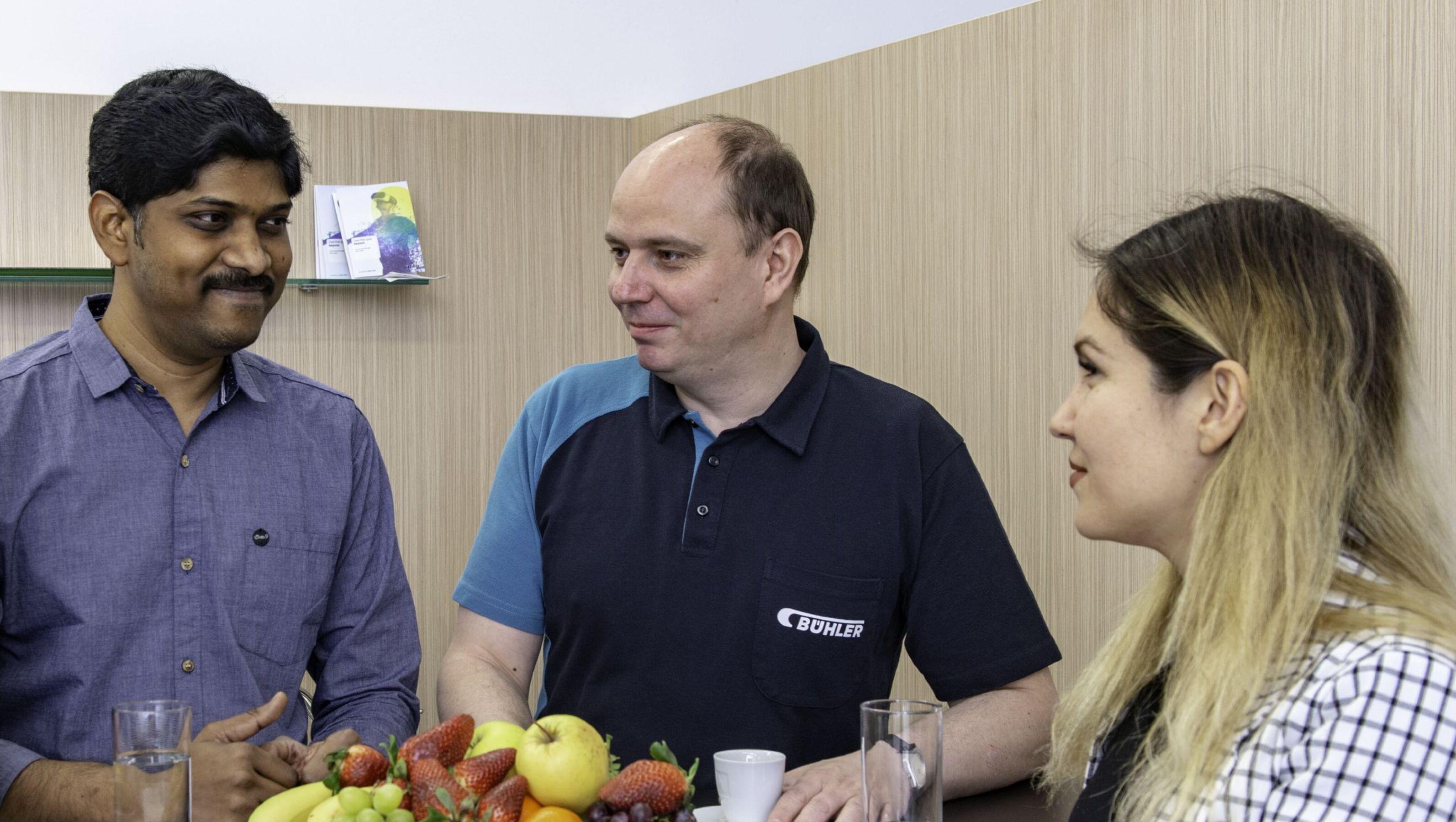 Un formador y un cliente de Bühler tomando café en la cafetería durante una pausa.