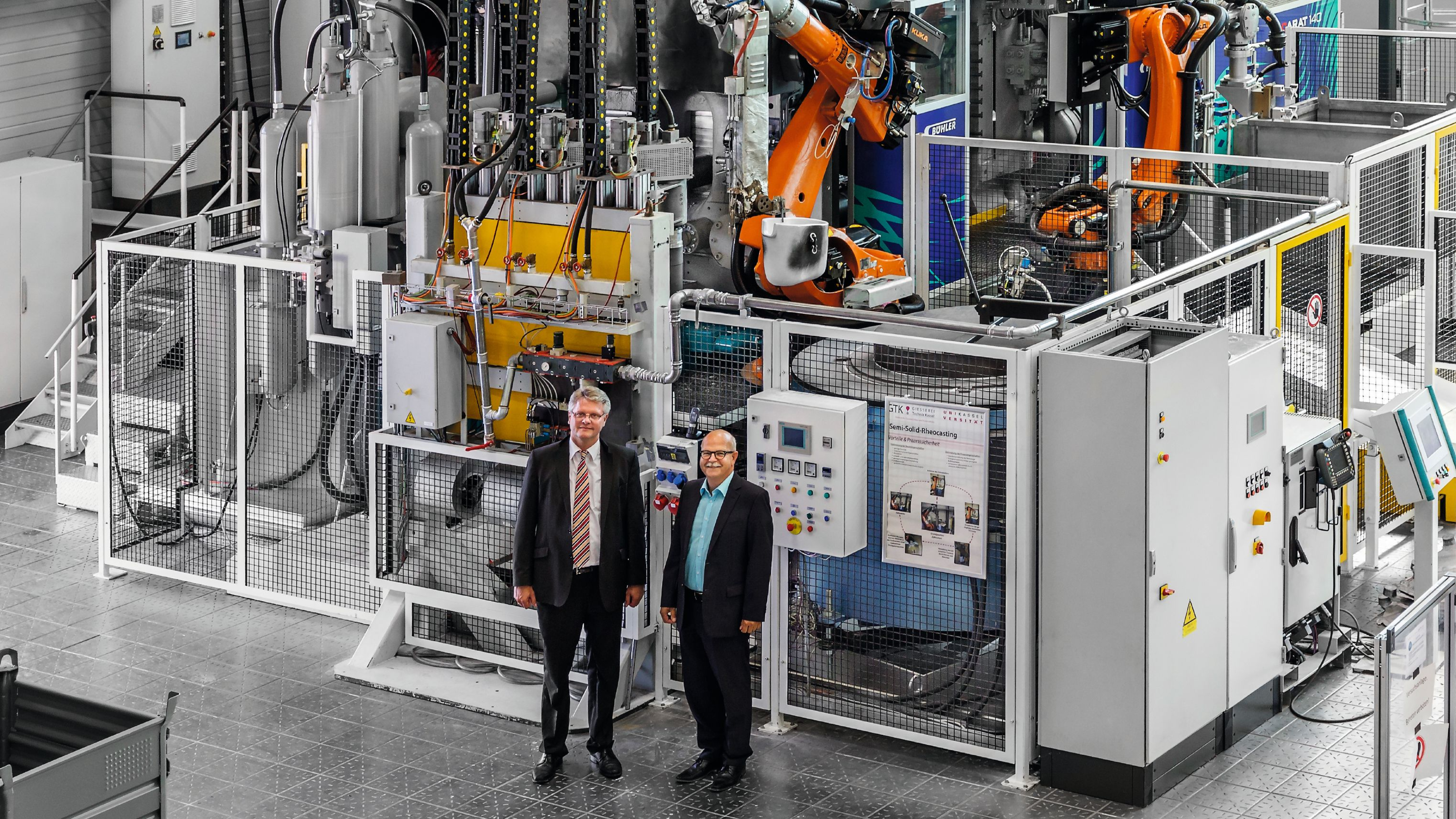 Professor Martin Fehlbier and Hartmut Schmidt are standing in front of the Carat die casting cell.